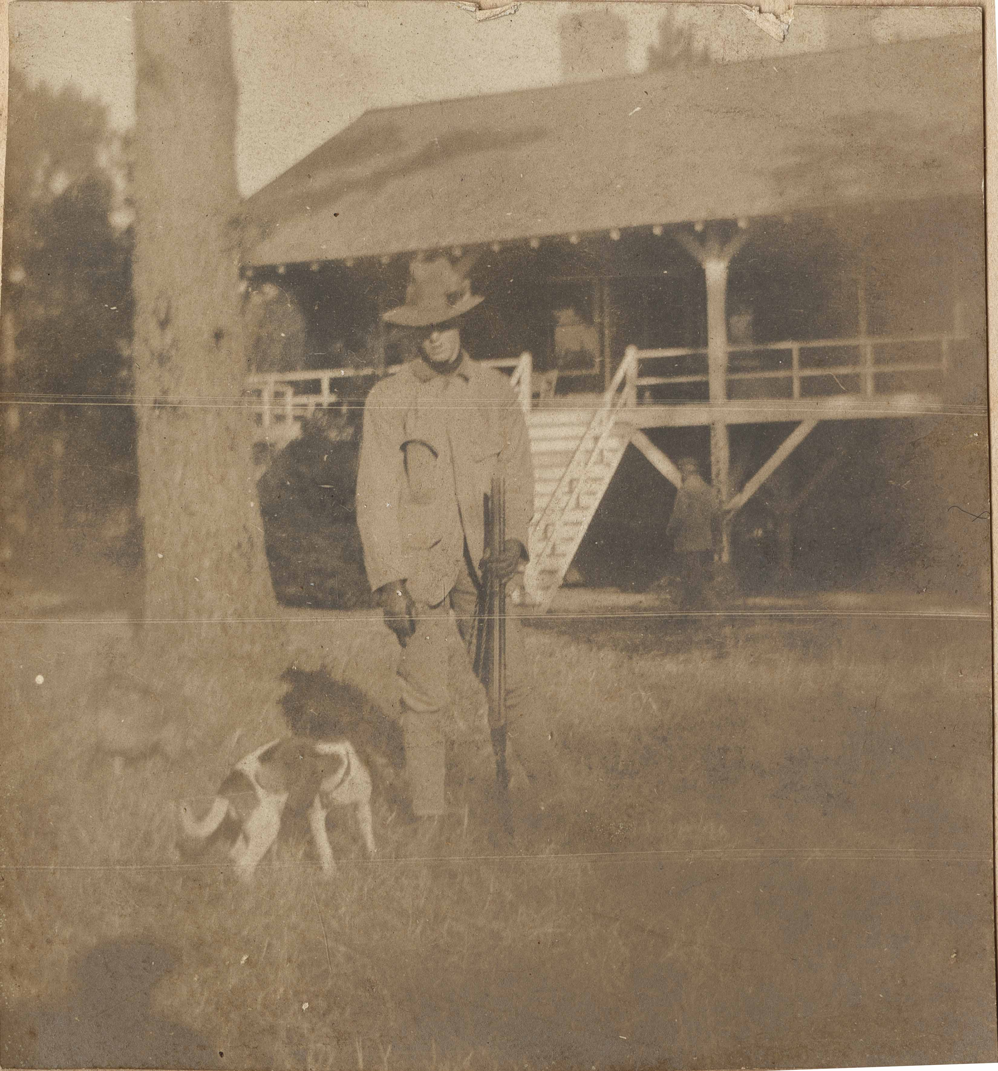 Pauline Donner with gun and dog in front of Main house