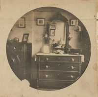 Room interior.  Chest of drawers and curved mirror.