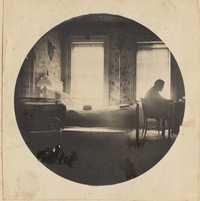 Man at table framed by light from two windows.