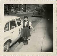 Unidentified girl, standing beside car