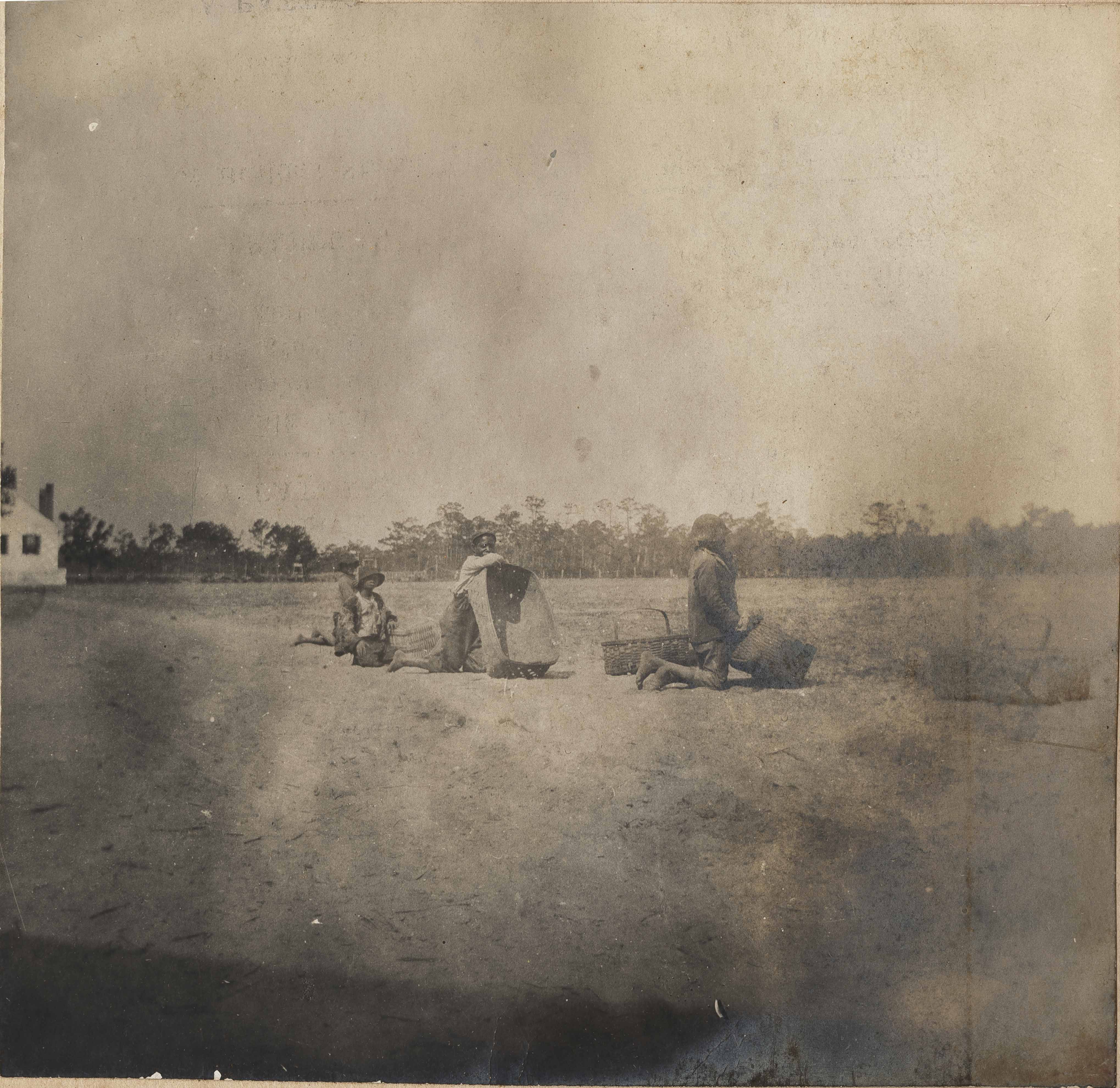 Men resting on baskets at edge of field