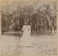 Unidentified woman with walking stick in woodland setting