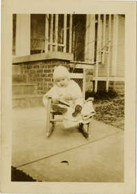 Infant sitting rocking chair outside