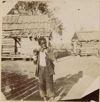 Boy with wooden flute in front of outbuildings