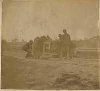 Men rolling equipment on logs